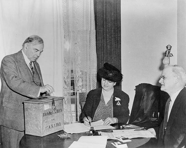 William Mackenzie King voting in the plebiscite on the introduction of conscription for overseas military service. 1942. National Archives of Canada, Ottawa. Library and Archives Canada. Web. 16 July 2015.